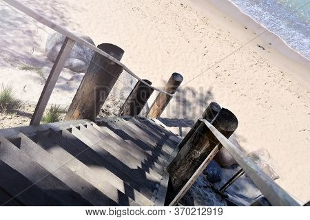 Wooden Staircase Descends Down To The Sandy Sea Beach In The Morning