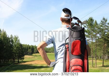 Golf Player Walking And Carrying Bag On Course During Summer Game Golfing.