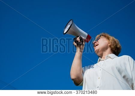 An Emotional Elderly Woman Pushes Demands Into A Megaphone. An Angry Retired Woman Is Fighting For T