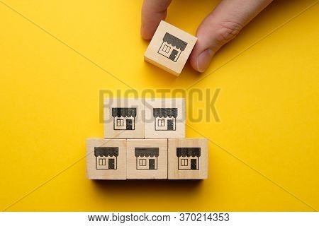 Concept Of Organizing A Chain Of Stores With Icons On Wooden Cubes