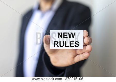 New Rules After Pandemic Concept. New Rules Text Words Inscription On White Paper Card In A Hand Of
