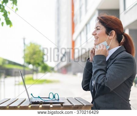 Happy Girl In A Suit Works Remotely On A Laptop Outdoors. A Business Woman Take Off A Medical Mask W