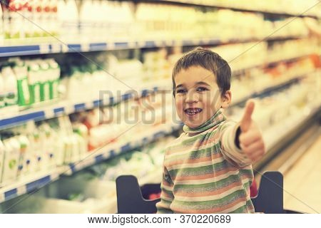 Happy Boy 4 Years In A Supermarket On The Background Of Shelves With Milk And Yogurt. Sun Rays. The