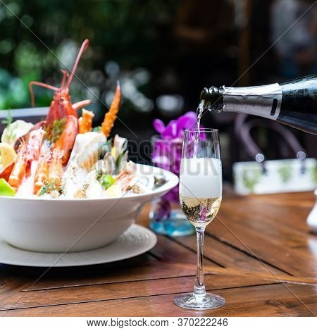 Waiter pouring white wine into wine glass and serving to customer in restaurant with big bowl seafood on ice in background. Restaurant gastronomy food and drink consumerism concept.