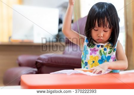 Asian girl child sewing in living room at home as home schooling while city lockdown because of covid-19 pandemic across the world. Home Scholling prepare for Preschool concept.