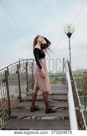 Woman Standing On The Rocky Shore Of The Sea. Girl Leaning On The Railing. Looking Away. Looking Str
