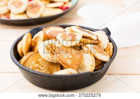 Trend Breakfast. Dutch Mini Pancakes In A Pan Close-up On A Wooden Table.