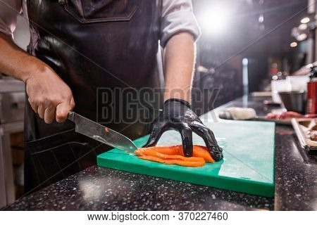 Close-up of unrecognizable chef in apron standing at counter and cutting salmon on cooking board at commercial kitchen