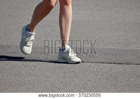 Slim Girl Running On A Street, Female Legs In Sneakers. Concept Of Workout, Woman Runner, Slimming I