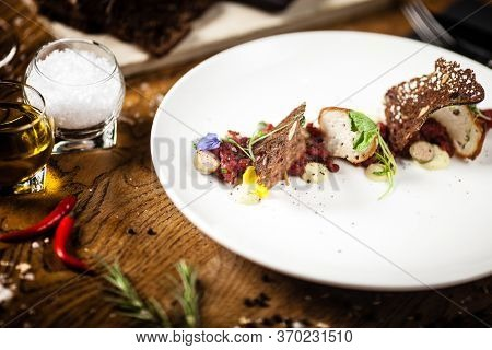 Steak tartare: Horseradish creme, black bread and baguette chips on a plate. Delicious healthy food closeup served for lunch on a table in modern gourmet cuisine restaurant.