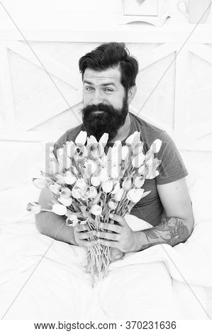 Make Surprise Concept. Gift For Spouse. Bearded Hipster In Bed. Spring In Bedroom. Man Hold Tulips B