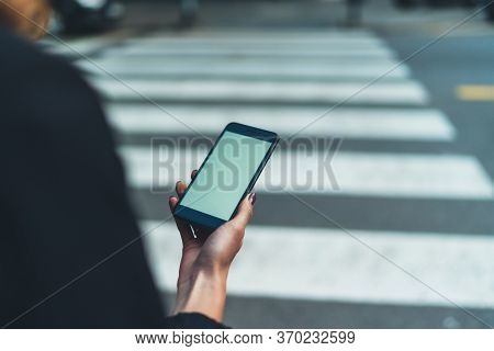 Top View Shot Of A Woman's Hands Using  Black Smart Phone With A Blank Screen While Standing At Cros