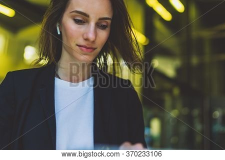 Successful Female Banker Using Wireless Earphones Outdoors Near His Office Background Yellow Neon Li