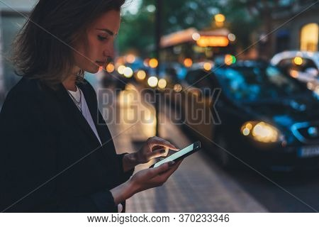 Elegant Woman Pointing On Screen Smartphone Background Headlights Auto In Night City Street, Tourist