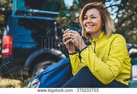 Girl Smiles And Enjoys Breakfast Outdoors Summer Nature, Tourist Hold Hand Mug Of Warm Tea During Re