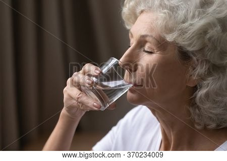 Thirsty Mature Woman Having Glass Of Water