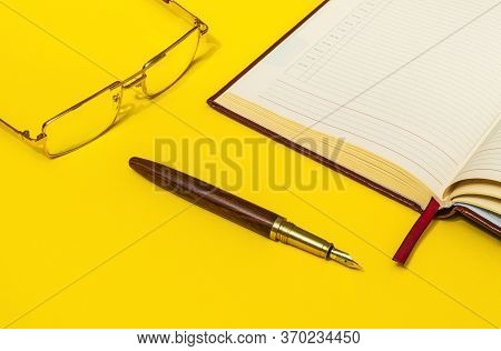 Gilt Pen And Glasses Rests Near Open Notebook For Notes Or Writing Text