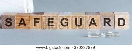 Safeguard Text On Wooden Table For Your Desing, Coronavirus Concept Top View. Grey Background. Safeg