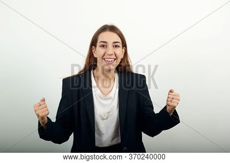 Arms Up Celebrating Success Fists In Exultation. Young Attractive Woman With Brown Hair In A Light T