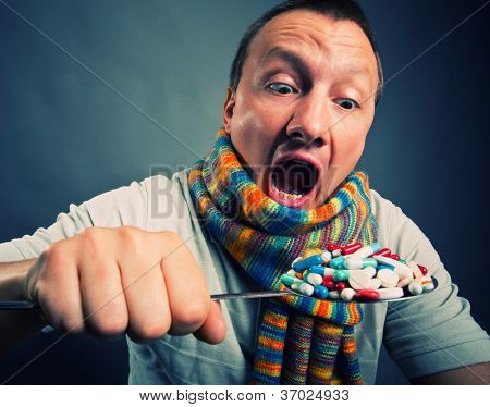Man eating pills and medicines with big spoon