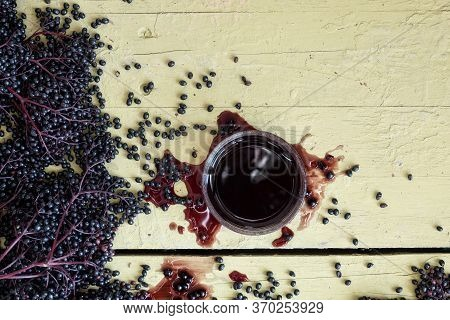 Fresh Ripe Violet Black Elderberries, Squeezed And Pressed And Elderberry Juice, On Rustic Grey Yell