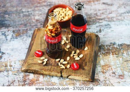 Kharkiv / Ukraine - June 6 2020: Selective Focus. Macro. Coca Cola Bottle With Peanuts. Peanuts With