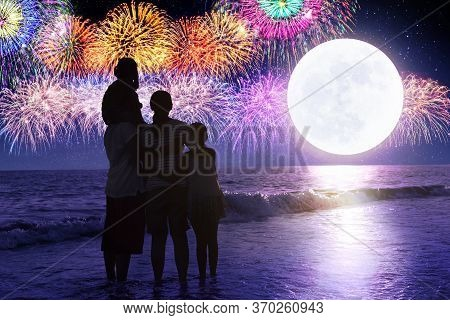 Happy Family Looking At Holiday Fireworks In Sky