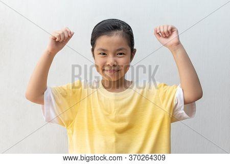 Asian Girl Standing Make Winner Gesture. Portrait