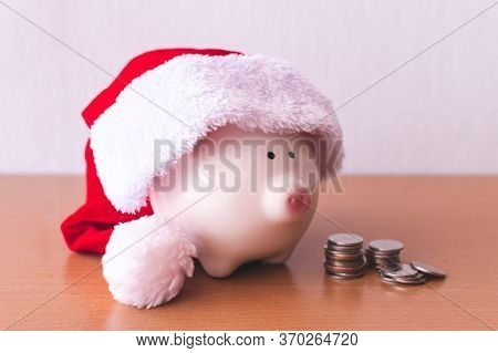 Piggy Bank With Santa Claus Hat And Coins On Wooden Table