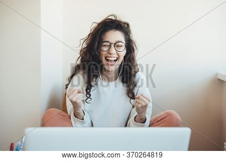 Lovely Young Woman With Eyeglasses And Curly Hair Smiling And Gesturing The Win Emotions In Front Of