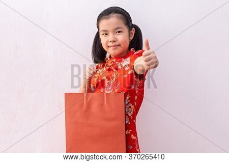 Asian Girl Wear Cheongsam Hold Shopping Paper Bag. Chinese New Year. Holiday And Celebrate Concept.