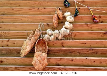 Russian Traditional Ancient Bast Shoes With Bunch Of Garlic And Rope With Hunging Wooden Spoons. Com