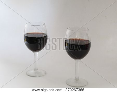 Pair Of Glass Stemware Filled With Red Wine On A White Background