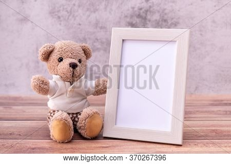 Teddy Bear With Picture Frame On Table Wooden. Valentine's Day Celebration