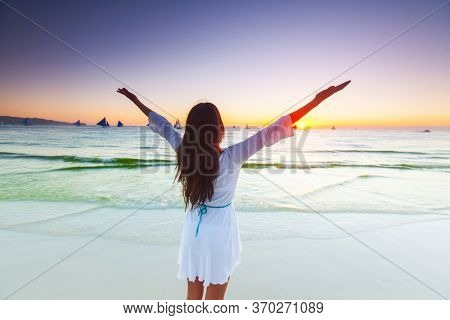 Woman standing on tropical sea beach with raised arms up and looking into a wide sea view with sail boats