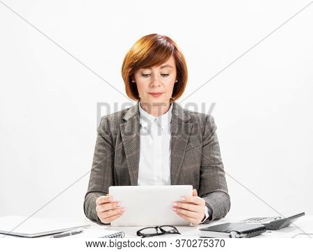 Business Woman Using Tablet Computer. Concentrated Accountant Sitting At Desk On White Wall Backgrou