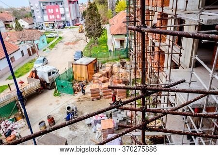 Rusty Scaffold Is Placed Against Edifice, Building Under Construction, Building Site In Background.