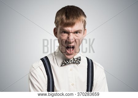 Frenzied Hipster Screaming With Anger. Emotional Redhead Boy Has Furious Facial Expression. Portrait