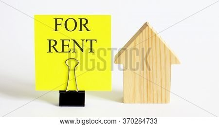 Table With Wooden Houses With The Word Rent. The Concept Of Rental Housing. Rent An Apartment Or Hou