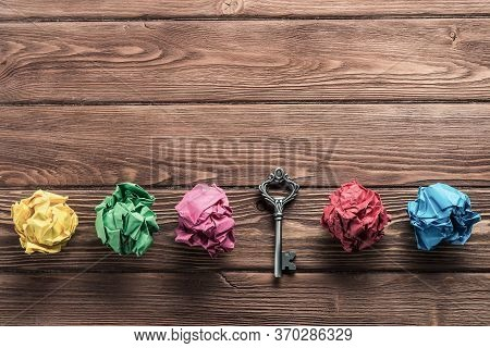 Vintage Key Among Many Balls Of Crumpled Paper On Wooden Table