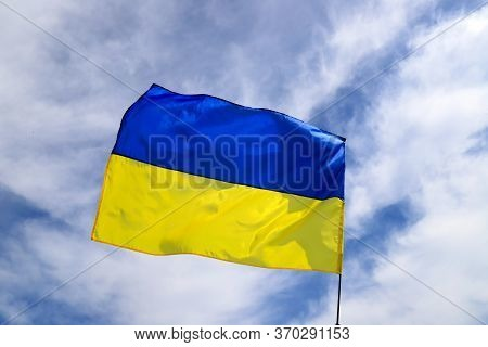 Large National Flag Of Ukraine Flies In The Blue Sky. Big Yellow Blue Ukrainian State Flag In The Dn
