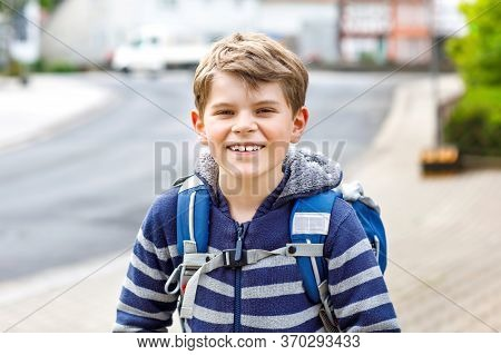 Happy Little Kid Boy With Backpack Or Satchel. Schoolkid On Way To Elementary School. Healthy Adorab