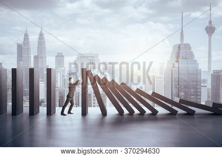 Businessman In Suit Pushing Blocks On Panoramic City  Background. Business And Challenge Concept.