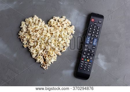 Popcorn In The Shape Of A Heart And Tv Remote On Grey Stone Background