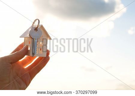 White Wooden Figure Of A House And Keys In Hand Against The Background Of The Sky . Dream Of Your Ho