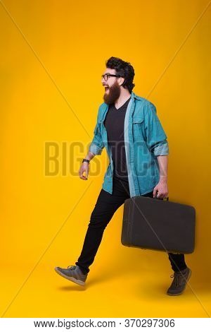 Full Lenght Photo Of Bearded Hipster Man Walking With Suitcase Over Yellow Background