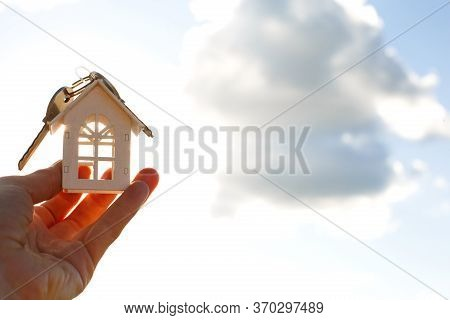 White Wooden Figure Of A House And Keys In Hand Against The Background Of The Sky. Dream Of Your Hom