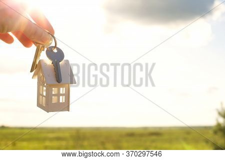 White Wooden Figure Of A House And Keys In Hand Against The Background Of The Sky And Field. Dream O