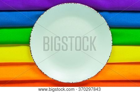 White Plate On A Rainbow Flag Lgbt Flag Of Six Colors For Design. Design Of The Dining Table For The