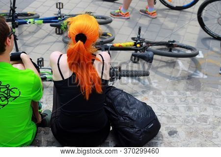 Young Guy And Girl Are Sitting Near Bicycles In The Street. Cyclists During A Cycling Sporting Event